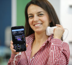 Image: Woman holds a ultrasound at her neck, connected with smartphone; Copyright: Messe Düsseldorf