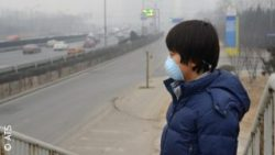 Image: A chinese child wearing a mask. In the background you see the smog; Copyright: ATS