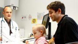 Photo: Man holding his baby talks to a physician