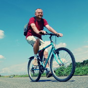 Photo: Man with rucksack on a bike, blue sky