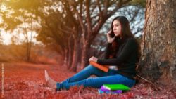 Image: Young woman is sitting under a tree in the park and uses her smartphone; Copyright: panthermedia.net/geargodz