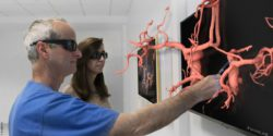 Image: Two physicians are looking at a model of a vascular system through 3D glasses; Copyright: Brainlab AG