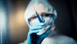 Image: A physician in a protective suit is holding up a syringe; Copyright: panthermedia.net/stockasso