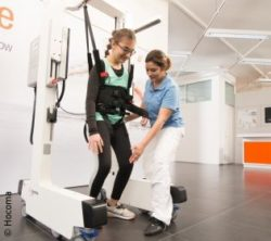 Image: Girl uses mobile robotic system to walk, next to her is a therapist; Copyright: Hocoma
