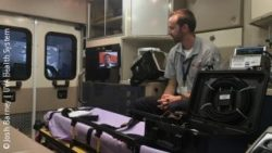 Photo: Paramedic Brett Schneider sits in an ambulance talking with a doctor via a tablet