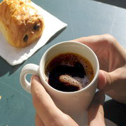 Photo: Hand holding a cup of hot coffee