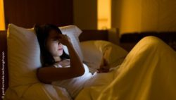 Image: A woman is looking at her smartphone in bed. She looks tired and exhausted; Copyright: panthermedia.net/leungchopan