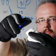 Photo: A man wearing arthritis simulation gloves