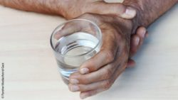 Image: One hand of an old man steadying the other hand that is holding a glass of water; Copyright: PantherMedia/Astrid Gast