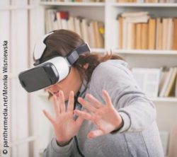 Image: Woman with VR glasses holding her hands fearfully in front of her body; Copyright: panthermedia.net/Monika Wisniewska
