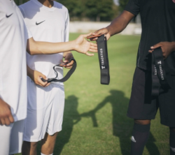 Photo: Referee in football hands out small devices with a belt to football players