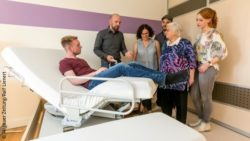 Image: several people standing around a bed with a stand-up function on which one person sits; Copyright: Ralf Lienert/Allgäuer Zeitung