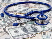 Photo: Stethoscope lying on dollar notes
