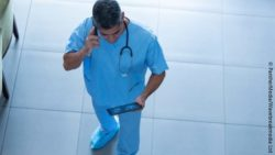 Image: A physician talking on the phone and holding a tablet computer in his hand is standing in the lobby of a hospital; Copyright: PantherMedia/Wavebreakmedia Ltd