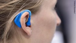 Image: Young woman with a blue plug in her ear; Copyright: Messe Düsseldorf