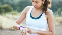 Image: A young woman is checking her smartwatch during running; Copyright: PantherMedia/gregorylee