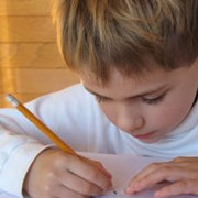 Photo: Young boy writes in his exercise book