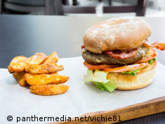 Photo: A large burger served with potato wedges