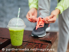 Photo: A runner ties his shoes next to a green smoothie