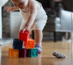 Image: Child playing with boxes on dusty floor; Copyright: Milken Institute School of Public Health at the George Washington University