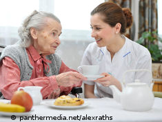Photo: Nurse helps an old woman to eat