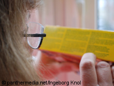 Photo: Woman with glasses tries to read a description