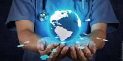 Image: A doctor is holding a globe in his hands; Copyright: panthermedia.net/everythingposs