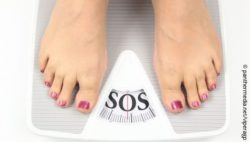 "Image: a woman standing on a scale saying ""SOS""; Copyright: panthermedia.net/viperagp"