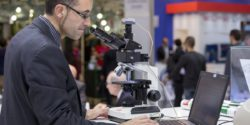 Image: Visitor of MEDICA works at a desk with microscope and laptop; Copyright: Messe Düsseldorf