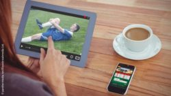 Image: Woman looks at the image of an injured soccer player on a tablet; Copyright: panthermedia.net/Wavebreakmedia Ltd.