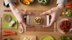 Image: View from above of a table with lots of food and two arms taking a picture of a dish with a smartphone; Copyright: panthemedia.net/stockasso