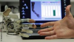 Image: robot hand and human hand are going to shake hands in front of a laptop; Copyright: MedUni Vienna