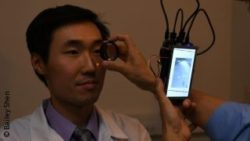 Image: The eye of an Asian man is scanned with a small camera; Copyright: Bailey Shen