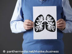 Photo: Man holding a printed iconic image of the lungs