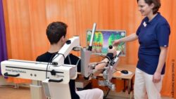 Image: Boy uses robot arm in front of a monitor with computer game, next to it stands the therapist; Copyright: Helios Klinik Hattingen