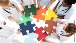 Image: A group of physicians is holding large colorful puzzle pieces in their hands and is putting them together; Copyright: panthermedia.net/Andriy Popov