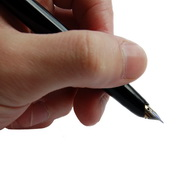 Photo: Hand holding a pen ready to sign