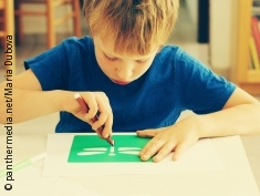 Photo: Little boy is drawing a butterfly