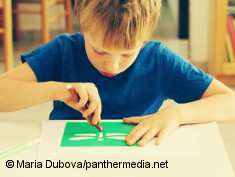Photo: Boy with autism sitting and drawing