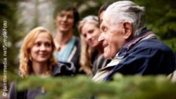 Image: A smiling old man is sitting next to a group of younger people; Copyright: panthermedia.net/SimpleFoto