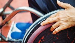 Image: Close-up of a hand on the wheel of a wheelchair; Copyright: panthermedia.net/apid