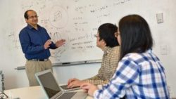 Image: Professor explains something at a whiteboard to two young people with laptops; Copyright: Virginia Tech