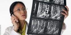 Photo: Asian female physician looks at MRT images and makes a phone call; Copyright: panthermedia.net/Edward Bock