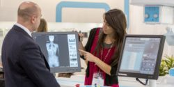 Image: An exibitor explains the software of an x-ray unit to a visitor of the MEDICA. She points on a screen; Copyright: Messe Düsseldorf