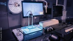 Image: A device with a large monitor and different control panels in a darkened laboratory; Copyright: Fraunhofer IPA – PAMB
