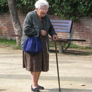 Photo: Old woman walking with a crooked stick