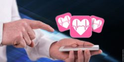 Image: Heart symbols are floating over a smartphone in the hand of a physician; Copyright: panthermedia.net/thodonal