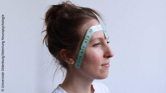 Image: A young woman is wearing a flat device made from printed electronics on her forehead; Copyright: Universität Oldenburg/Abteilung Neuropsychologie
