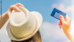 Image: Young woman with a white hat is holding her European Health Card in front of the blue sky; Copyright: PantherMedia/rochu_2008