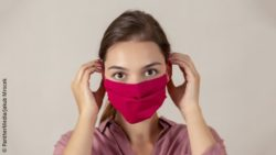Image: A nurse is donning a red cloth mask; Copyright: PantherMedia/Jakub Mrocek